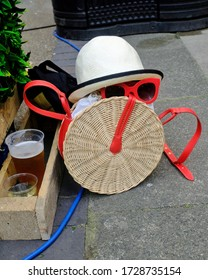 A hat, sunglasses and straw bag create a summertime scene in an English beergarden.