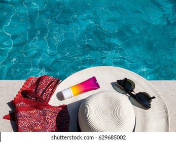 Hat, sunglasses and sunscreen at the side of swimming pool, summer travel concept