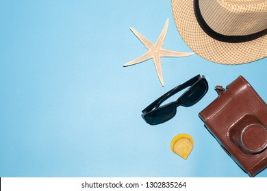 hat, vintage camera, sunglasses, starfish, shell isolated on blue background, vacation resort concept
