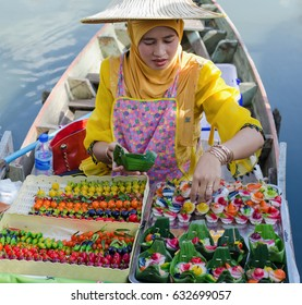 HAT YAI, THAILAND - MARCH 30 2014: A Thai Muslim woman selling Thai sweets on th boat at Klong Hae floating market in Hat Yai, Thailand.