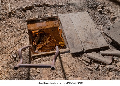 A hatch in the floor leading to a deep cellar
