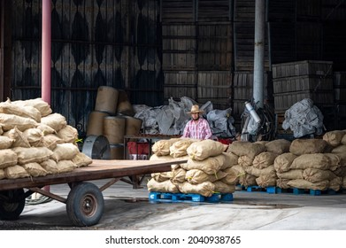 HATCH, NEW MEXICO - SEPTEMBER 4, 2021: A farm worker unloads bushels of freesh harvested chiles in burlap bags during the annual Hatch Chile Festival.