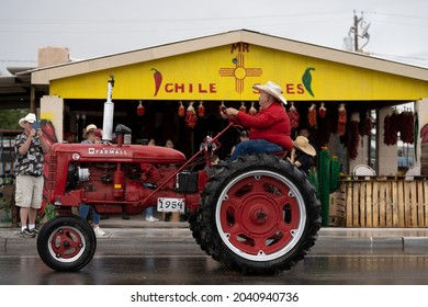 HATCH, NEW MEXICO - SEPTEMBER 4, 2021: A farmer drives a red tractor in the parade during the annual Hatch Chile Festival.