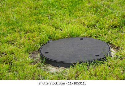 The hatch of the well is closed with a round metal cover. Grass grows around the hatch