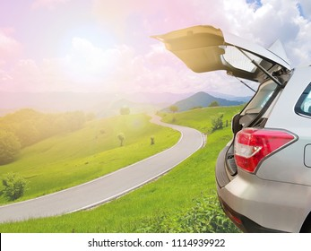 Hatchback car, open car trunk with empty road, blue sky, green grass and mountain view in beautiful nature background with tone vintage retro, Travel or relax holiday concept.