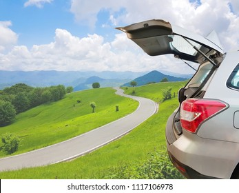 Hatchback car, open car trunk with empty road, blue sky, green grass and mountain view in beautiful nature background, Travel or relax holiday concept.