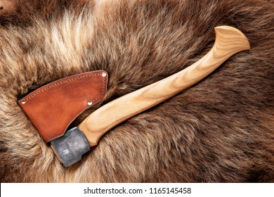 Hatchet on bear skin. Metal ax with leather case on a bear hide.