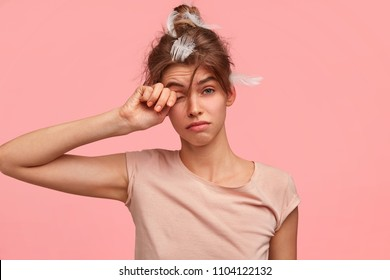 I hate awake too early! Attractive European young female rubs eyes and has sleepy expression, didsn`t have enough sleep at night as worked long at diploma paper, needs good rest, stands indoor.