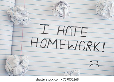 I Hate Homework. Phrase I Hate Homework on notebook sheet with some crumpled paper balls on it. Close up.