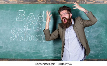 Hate school. Teacher goes mad about schooling. Teacher or educator stands near chalkboard with inscription back to school. Teacher unhappy shouting hysterically face. Man refuses begin work at school.