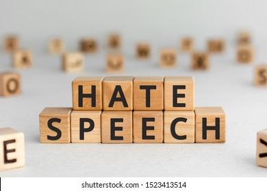 Hate speech - words from wooden blocks with letters, speech that attacks a basis attributes such as race, religion, or gender identity hate speech concept, random letters around, white  background