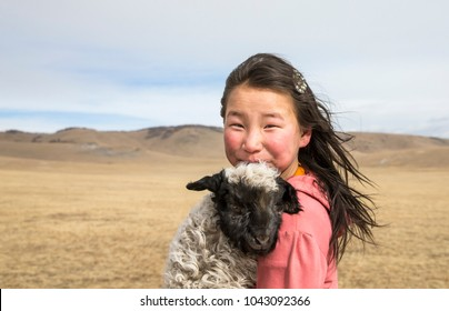 Hatgal, Mongolia, 2nd March 2018: mongolian girl carrying a baby sheep in a steppe