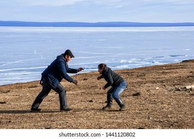 Hatgal, Mongolia, Febrary 25, 2018: two men playing outside in Mongolian wrestling in winter near frozen lake