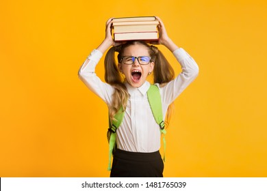 Hating School. Angry Schoolgirl Shouting Holding Books On Head On Yellow Studio Background. Copy Space