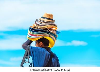 Hats seller on a sandy beach, Boracay, Philippines. With selective focus