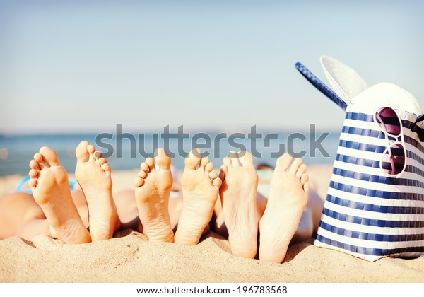 hats and summer concept - three women lying on the beach with straw hat, sunglasses and bag