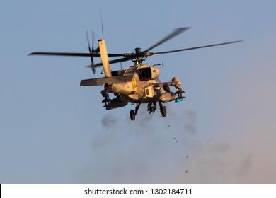 Hatzerim, Israel 06 28 2018: Israeli Air Force AH-64 Apache combat helicopter firing guns during an airshow at Hatzerim, close to Beersheva Israel