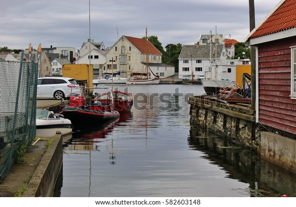 Haugesund, Norway - August 4, 2015: Scenery with wooden houses and boats on the fjord Smedasund. In the 19th century the town was famous for its herring fishery. Scandinavia, Europe.