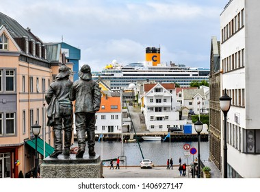 Haugesund, Norway – July 18, 2017: Downtown of Haugesund in Norway. In the foreground there is a statue of two fishermen and in the background the cruise ship Costa Favolosa of Costa Cruises.