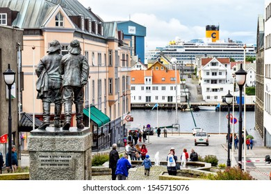 Haugesund, Norway – July 18, 2017: Downtown of Haugesund in Norway. In the foreground there is a statue of two fishermen and in the background the cruise ship Costa Favolosa.