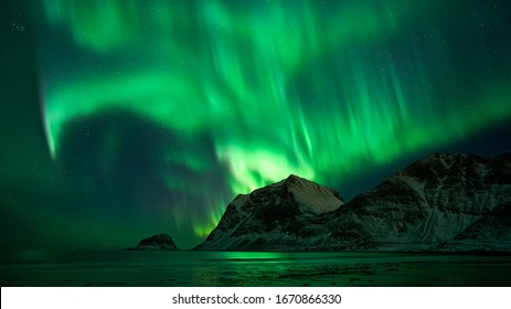 Hauklandbeach, Lofoten / Norway - March 7th 2019: huge northern lights / aurora outbreak over fjord at hauklandbeach near Leknes. lights dazzled green, white over mountains of fjord Vikbukta