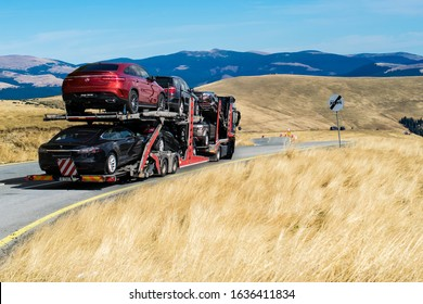 Hauling cars. Car-carrying trailer transporting Mercedes and Tesla electric cars. Mercedes-Benz/ Junge Sterne.  A beautiful road through the mountains. Romania, October, 13, 2019