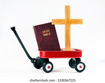Hauling the old wooden cross and the Holy Bible in a little red wagon.
