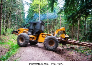 Hauling wood in the forest by a grapple skidder, motion of hauling machine and hauled wood blurred