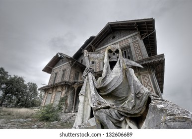 Haunted house. Abandoned and ruined manor with a gream reaper statue in foreground