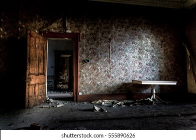 Haunted room with light coming through window. Vintage wallpaper torn and rotting from the walls. Dust lay untouched on floorboards for years.