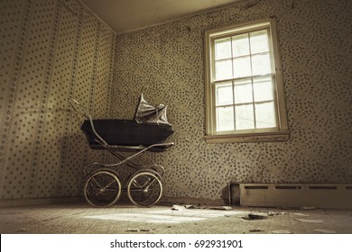Haunting image of an old fashioned baby buggy in the corner of an empty room. Natural light from the nearby window. Slight grunge effect creating dark edges.