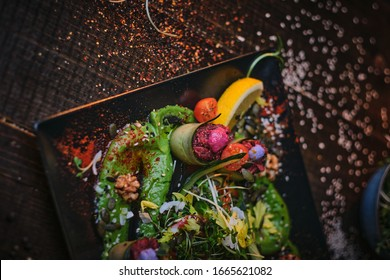 Haute cuisine vegetarian plate of appetizer rolls and a bowl of herbs served on a wooden table next to salt grinder in a restaurant - Shutterstock ID 1665621082