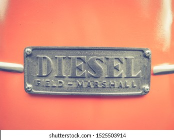 Haute-Garonne, France - June 21, 2019: Diesel power. Field Marshall logo (hood ornament) silver on red on front of an old tractor. Detailed closeup of metal symbol of British machinery manufacturer