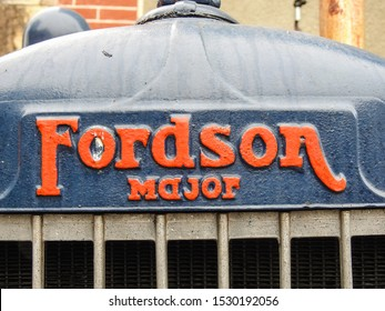 Haute-Garonne, France - June 30, 2019: Fordson logo (hood ornament) of an old Major tractor model manufactured by the Ford Motor Company. Closeup of company name in red on blue background