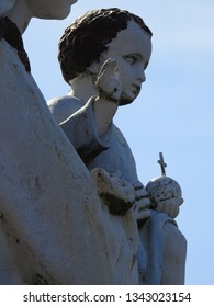 Haute-Garonne, France - March 3, 2019: Blessed Virgin Mary holding Baby Jesus in her arms with globus cruciger (orb and cross) raising arm in gesture of blessing. Statue against blue sky background
