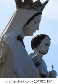 Haute-Garonne, France - March 3, 2019: Blessed Virgin Mary wearing crown holding Baby Jesus in her arms, holding globus cruciger (orb and cross) raising arm in gesture of blessing. Statue against sky