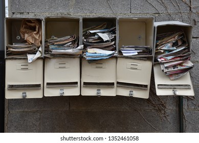 Hauts-de-France/France-August 26 2018: French mail boxes — unwanted mail build up in a group of five neglected mail boxes