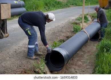 Hauts-de-France/France-May 18 2018: A large bore evacuation pipe being positioned on a bed of sand in a trench alongside a rural road