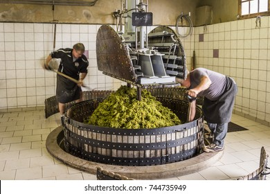 Hautvillers, France - August 11, 2017. Pressing the grapes with an old press with two working men in the Pressoir in Champagne village Hautvillers near Reims and Epernay.