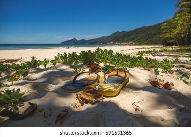 Havaianas on the sand under the palms shadows on the beach. Ilha Grande, Rio de Janeiro, Brazil 02.12.2014
