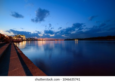 Havana bridge in Kiev at night with colorful illumination, beautiful clouds and reflection in Dnieper river. Wide angle