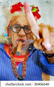 HAVANA – CIRCA DECEMBER 2008: An eccentric old Cuban lady smokes cigar and points finger circa December 2008 in Havana, Cuba.