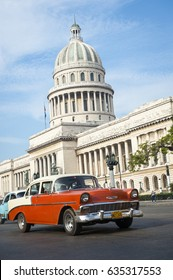 HAVANA - CIRCA JUNE, 2011: Classic American car from the 1950s passes in front of the iconic Capitólio building, a city landmark.