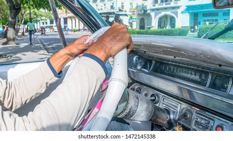 Havana city, Havana, Cuba-July 22, 2019: Driver's hand over the wheel of an old American car being used as a tourist taxi. Obsolete cars in working condition are a tourist attraction in Cuba. Panorama