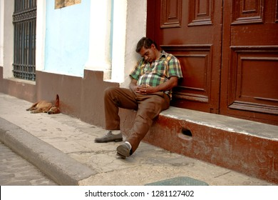 Havana, Cuba. 02/09/2014 The man sleeps on the street, sitting on the step at the front door of the house. His dog is sleeping next to him. Editorial. Sweet dream. Happy oblivion. Coworking. Humor.