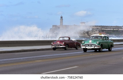 HAVANA - CUBA / 03.07.2017: Vintage American cars with waves splashing over Malecon Vedado Havana Cuba