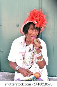 HAVANA - CUBA / 03.08.2017: Od Cuban woman with red hair ribbon smokes a Havana cigar, La Habana, Cuba