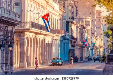 Havana, Cuba - 04 October, 2018: Street life with cuban flags, american blue 1953 Chevrolet Bel air and Buick Special vintage cars in the warm evening sun in Havana City Cuba - Serie Cuba Reportage