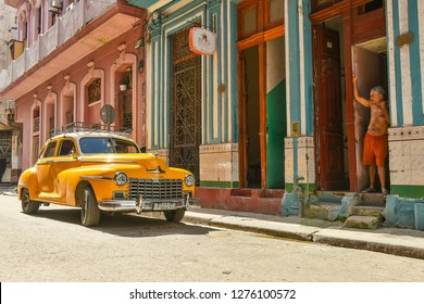 Havana, Cuba, 2.12.2018: Old Man watching yellow Oltimer