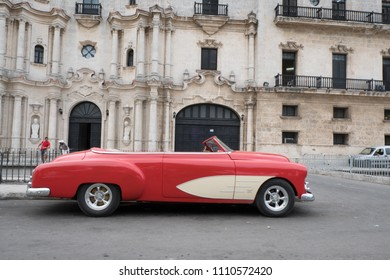 Havana, Cuba -26 April 2018: Side view of a 1950s Chevrolet Bel Air parked in front of an old building in Old Town. Two men chatting leaning on a fence in the background.